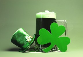 Celebrate all the fun and luck of the Irish of St Patrick's Day with a glass stein of green beer, a large shamrock and leprechaun hat on a green background. Vertical with copy space for your text here.